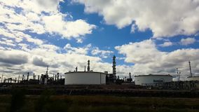Time lapse of clouds over refinery. A time lapse and pan over a refinery in Denver, Colorado stock footage