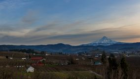 Time lapse of clouds over snow covered Mt. Hood and pear orchards at sunset 4k stock video