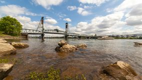 Time lapse of clouds over Willamette River with Hawthorne Bridge in Portland Or. Time lapse of moving  white clouds and blue sky water reflection over Willamette stock footage
