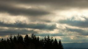 Time lapse of clouds and sunbeams over mountain landscape in Beaverton OR 4k uhd. Time lapse movie of moving dark stormy clouds sky sunrays and sunbeams over stock video footage