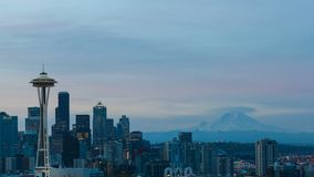 Time lapse of clouds and sunrise over Seattle WA with snow covered Mt. Rainier. Ultra high definition 4k time lapse movie of clouds and lights over city of stock video footage