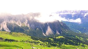 Time lapse of the clouds on the top of the beautiful Dolomites in sunny day. With the green hilly field and small village in the valley seen from the Secada stock footage