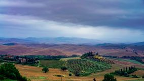 Time lapse with clouds and typical farmhouse in San Quirico d`Orcia in Italy. Cloudy morning in the Tuscan hills at San Quirico d`Orcia with view on Belvedere stock video footage