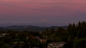 Time lapse of colorful sunset over Mt. Hood and residential homes in Happy Valley OR 4k uhd. Time lapse of moving clouds and colorful sunset over residential stock footage
