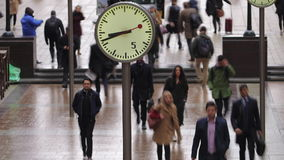 Time lapse of commuters walking past clocks, Canary Wharf, London stock video footage