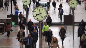 Time lapse of commuters walking past clocks, Canary Wharf, London stock video