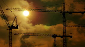 Time lapse of construction cranes silhouettes at sunset light build develop stock video