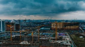 Time lapse construction site against the backdrop of the cityscape, cranes and builders are working.  Royalty Free Stock Photography