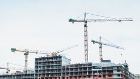 Time lapse cranes and builders are working on the construction site.  Royalty Free Stock Image