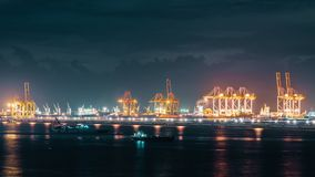 Time-lapse of cranes loading shipment containers in cargo shipping port at night. Import or export business, logistic industry stock video
