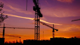 Time lapse  cranes working in construction site at dusk,  pan.Craner climbing stock video footage