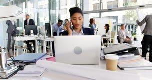 Time lapse de la empresaria que come café mientras que trabaja en el escritorio