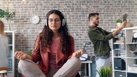 Time lapse de la muchacha bonita en los auriculares que se sientan en el escritorio de oficina en la posición de loto almacen de metraje de vídeo