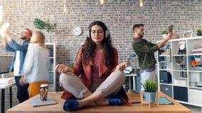 Time lapse de la muchacha que escucha la música en actitud del loto en los auriculares que llevan de la tabla almacen de video