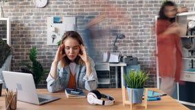 Time lapse del empleado deprimido de la muchacha sufffering de dolor de cabeza en oficina almacen de metraje de vídeo