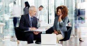 Time lapse del hombre de negocios y de la empresaria que obran recíprocamente con uno a