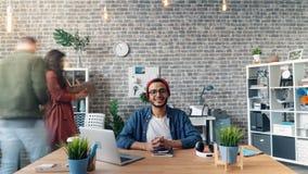 Time lapse del individuo feliz que se sienta en el escritorio de oficina que sonríe mirando la cámara almacen de video