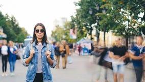 Time lapse del turista solo de la muchacha que se coloca en ciudad moderna con la gente que mueve alrededor y que mira la cámara  metrajes