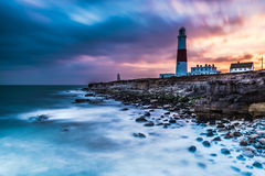 Time lapse of dramatic sunset and Portland Bill lighthouse. On rocky shore at Portland, Dorset, UK Stock Photos