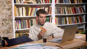Time lapse of enjoyable caucasian male is sitting with his legs on desktop and looking at computer while drinking coke. And biting tasty pizza slice, books stock video footage