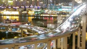 Time lapse fast cars on overpass bridge,urban building & shipping on river. Aerial freeway busy city rush hour heavy traffic jam highway Shanghai at night stock video footage