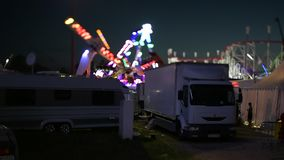 Time lapse fast motion night scene of amusement park with parked white trucks and Ferris wheel. Strasbourg, France - Circa 2018: Time lapse fast motion night stock footage