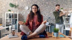 Time-lapse of employee listening to music enjoying break in lotus pose on desk stock footage