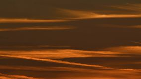 Time lapse of flying airplane leaving wake against dramatic red sunset sky stock footage