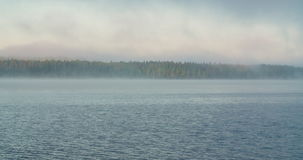 Time lapse of fog covering up a lake. Time lapse of fog covering up a large lake with forest in background stock video