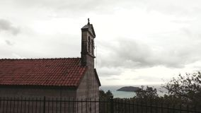 Time lapse - gloomy clouds float past the christian chapel. With a cross standing on the edge of the city. Concept of christian faith and religion stock video