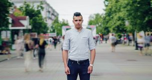 Time lapse of good-looking young Arab with serious face standing alone in street stock video footage