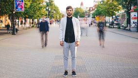 Time-lapse of handsome young man in stylish clothing standing in the street of big city and looking at camera with