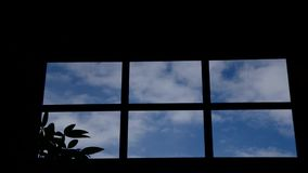 Time lapse through a kitchen window of white clouds and blue sky. stock video footage