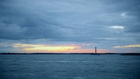 Time lapse of lighthouse with dramatic clouds. And yellow and orange light coming through them stock footage