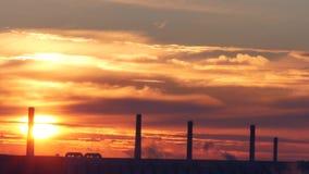Time Lapse med röd soluppgång för morgon över en fabrik med moln av rök lager videofilmer