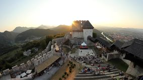 Time lapse of medieval games attendees with the castle in the background. CELJE, Slovenia - August 2012: Medieval festival with reenactment of fighting knights stock video footage