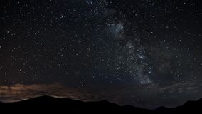 Stars moving in night sky over mountains time lapse. Milky way astronomy. Timelapse video of starry night with milky way galaxy moving over mountains and low stock video
