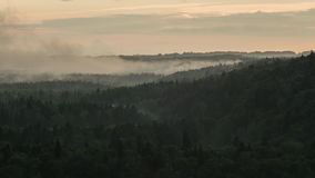 Time lapse of mist rising over a valley as the Sun sets. Time lapse of mist and clouds rising from a dense forest valley in Sigulda, Latvia stock video