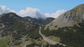 Time lapse. Montenegro, National park Lovcen. Clouds float over the mountain peaks, сars drive on road. Beautiful landscape stock video