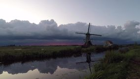 Time lapse of the motion and development of storm clouds at sunset over traditional dutch landscape with water and windmill. Classic dutch scene with windmill stock video footage