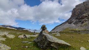 Time lapse motion. Stone pyramid on a hiking trail in the mountains, flying fluffy puffy white clouds in the bright blue sky. The concept of travel in the stock video footage