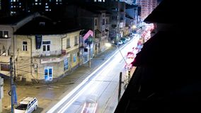 Time lapse of moving cars in the night city from balcony view. Time lapse of fast moving cars in the night city leaving neon lights in the back from balcony view stock video