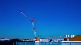 A time lapse of moving cranes behind the blue sky at the under construction wide shot. Moving cranes behind the blue sky at the under construction. Niiza-shi stock video footage