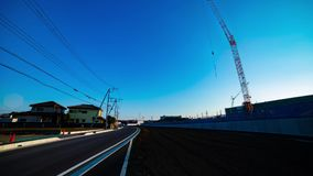 A time lapse of moving cranes behind the blue sky at the under construction wide shot. Moving cranes behind the blue sky at the under construction. Niiza-shi stock footage