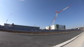 A time lapse of moving cranes behind the blue sky at the under construction wide shot. Moving cranes behind the blue sky at the under construction. Niiza-shi stock video