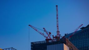 A timelapse of cranes at the under construction behind the blue sky in Tokyo. A time lapse of moving cranes at the under construction behind the blue sky stock video