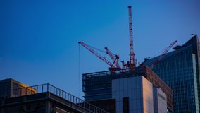 A timelapse of cranes at the under construction behind the blue sky in Tokyo. A time lapse of moving cranes at the under construction behind the blue sky stock footage