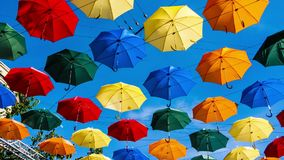 Time lapse of multi-colored umbrellas in sky above the street. Alley floating umbrellas. stock footage