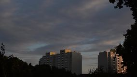 Time lapse of nightfall in a city. It gets dark. Clouds move over residential buildings with tree silhouetets in foreground stock footage
