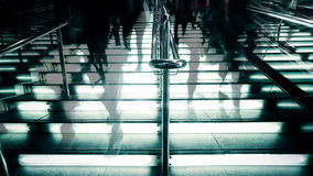 Time lapse people silhouettes moving at illuminated stairway at modern shopping mall, Hong Kong. High contrast, blur effect